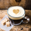 Small cup of espresso coffee in glass with heart drawning on fo — Stock Photo