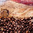 Coffee beans on old natural wooden background — Stock Photo