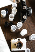 Photo spools and filn cameras on a wooden table — Stock Photo