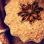 Cinnamon sticks, nuts and star anise on brown sugar, macro. — Stock Photo
