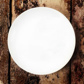 White plate on wooden old table, top shoot — Zdjęcie stockowe