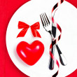 Stock Photo: Red Heart on a white plate plate on festive napkin with red bow.