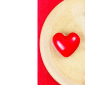 Red Heart on golden plate on red tablecloth — Stock Photo
