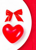 Red Heart on a white plate plate on festive napkin with red bow. — Stock Photo