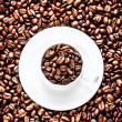 White Coffee Cup with saucer full of Roasted Coffee Beans — Stock Photo