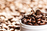 White Cup full of roasted coffee beans — Stock Photo