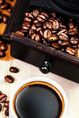 Cup of coffee with roasted beans — Stock Photo