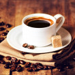 Stock Photo: Cup of coffee with coffee beans on wooden table