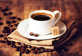 Cup of coffee with coffee beans on wooden table — Stock Photo