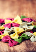Raw Bow tie pasta  with variety of flavours — Stock Photo
