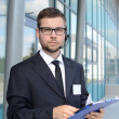 Stock Photo: Young male call center operator in suit
