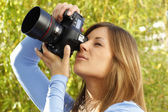 Attractive woman taking pictures outdoor — Stock Photo