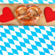 Red hearts and pretzel on bavarian checkered background — Stock Photo #26384337