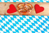Red hearts and pretzel on bavarian checkered background — Stock Photo
