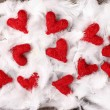 Red hearts laying on white feathers — Stock Photo #26393247