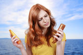 Red haired woman with sun lotion — Stok fotoğraf