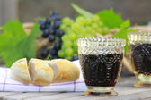 Beautiful still life with glasses, grapes and bred — Stockfoto