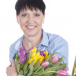 Senior woman with spring flowers — Stock Photo