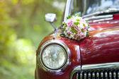 Wedding bouquet on vintage wedding car — Stock Photo