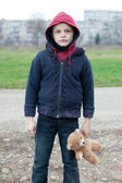 Young homeless boy on the street with bear — Stock Photo