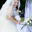 Happy bride signing the wedding contract — Stock Photo