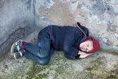 Homeless boy sleeps under the wall — Stock Photo