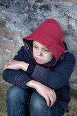 Homeless boy leaned against the wall — Stock Photo