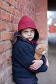 Homeless boy leaned against the wall with bear — Stock Photo