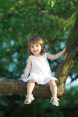 Liten flicka sitter på trädet — Stockfoto