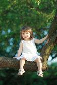 Meisje, zittend op de boom — Stockfoto