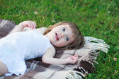 Little girl lying on the blanket — Stock Photo