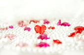 Red and purple cristal hearts on pearl-like balls — Stock Photo