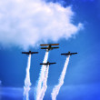 Stock Photo: Four propeller planes skywriting at airshow