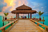 Tropical hut on water at sunset — Stock Photo