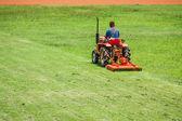 Man on mower cutting grass — Stock Photo