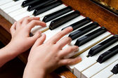 Child hands playing piano — Stock Photo