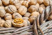 Cracked walnut in wicker basket — Foto de Stock