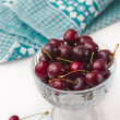 Cherries on glass bowl with blue serviette — Stock Photo