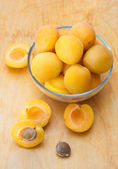 Ripe apricots in glass bowl on wooden board — Stock Photo