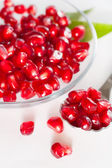 Ripe pomegranate seeds on a glass plate. — Stock Photo