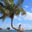 Girl on the bending palm tree in the Bahamas — Stock Photo