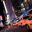 Stock Photo: New York city yellow cabs at night