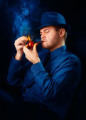 Man with Hat Lighting His Pipe with a Match — Stockfoto