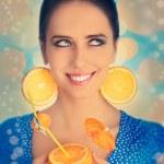 Girl with Orange Drink and Orange Slice Earrings — Stock Photo #46365183