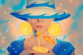 Girl with Orange Drink and Orange Slice Earrings Wearing Hat — Stock Photo