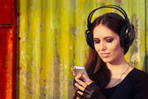 Girl with Big Headphones and Smart Phone on Grunge Background — Stock Photo