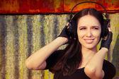 Girl with Big Headphones on Grunge Background — Stock Photo