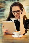 Mulher jovem com óculos e tablet tomando café — Foto Stock