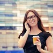Young Woman with Coffee Cup on the Phone Out in the City — Stock Photo #49871309