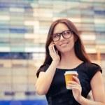 mujer joven con la taza de café en el teléfono en la ciudad — Foto de Stock   #49871309